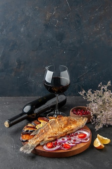 Вид снизу, жареная рыба, жареные баклажаны, нарезанный лук на деревянной доске, бутылка вина и бокал на темном фоне, свободное пространство