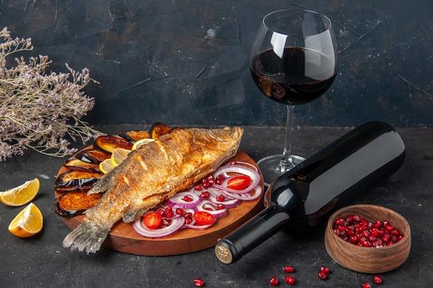 Вид снизу, жареная рыба, жареные баклажаны, нарезанный лук на деревянной доске, бутылка вина, лежа и бокал на темном фоне