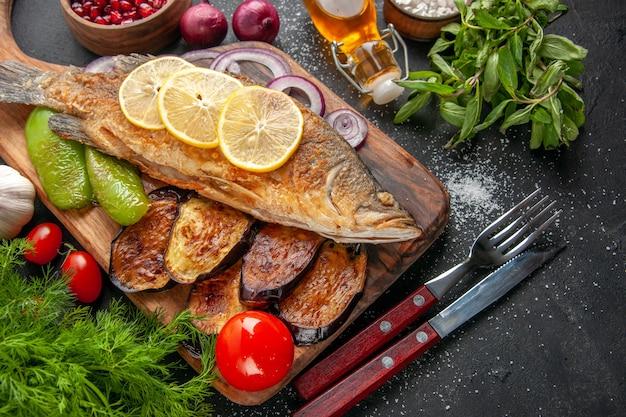 아래쪽 보기 생선은 나무 판자에 튀긴 가지 양파 고추를 튀긴 작은 그릇 포크와 나이프 토마토 오일 병 민트 딜을 어두운 배경에 튀깁니다.