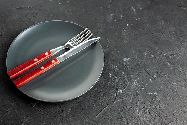 Vista dal basso una forchetta e un coltello su un piatto rotondo nero su uno spazio libero di superficie scura