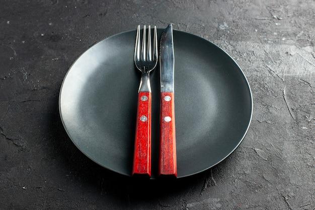 Vista dal basso una forchetta e un coltello su un piatto rotondo nero su un tavolo scuro