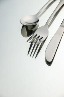 Cucchiaio coltello forchetta vista dal basso su superficie chiara