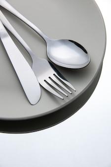 흰색 절연 된 표면에 접시에 하단보기 포크 스푼 나이프