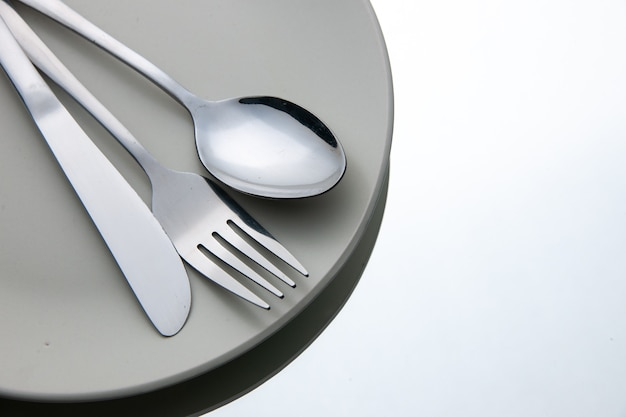 Bottom view fork spoon knife on plate on white isolated surface copy place
