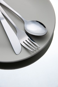 Bottom view fork spoon knife on plate on white isolated surface