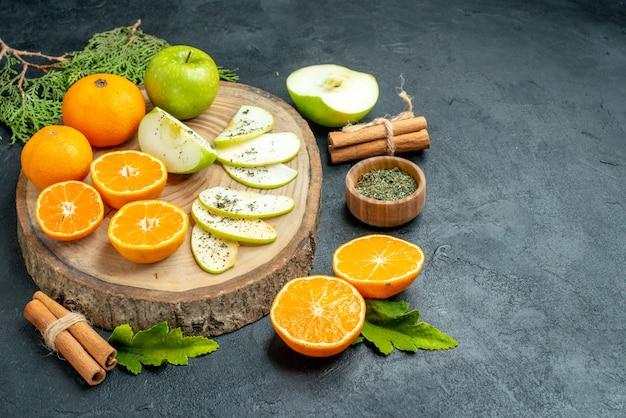 底面図新鮮なリンゴとオレンジのスライスを木の板に乾燥ミントパウダーをボウルに入れシナモンスティック松の木の枝を黒いテーブルの空きスペースに