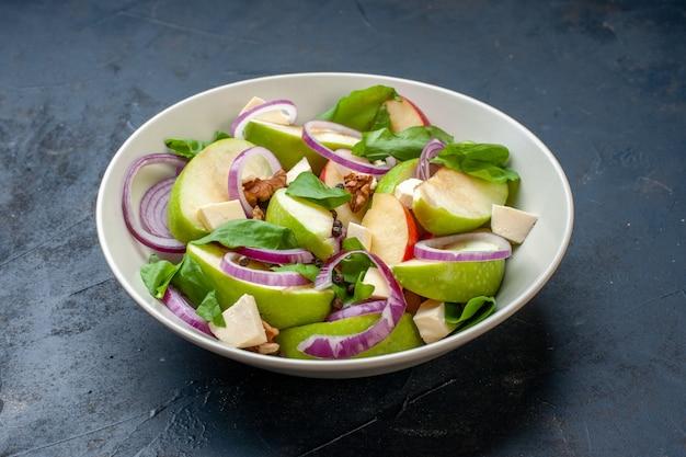 Салат из свежих яблок в миске на темно-синем столе, вид снизу