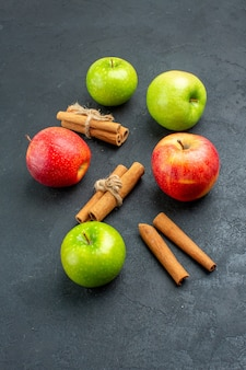 Vista dal basso mele fresche bastoncini di cannella su superficie scura