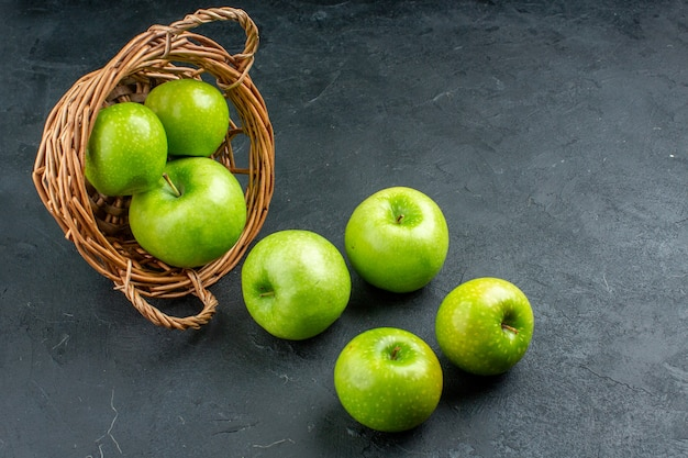 Vista dal basso mele fresche sparse dal cesto di vimini sullo spazio libero della superficie scura dark