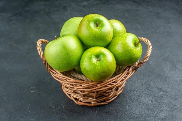 Vista dal basso mele fresche in cesto di vimini su superficie scura