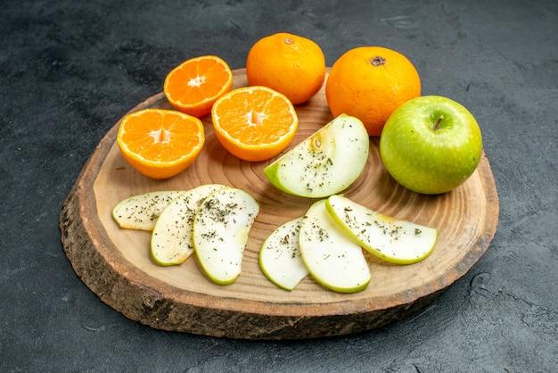 底面図黒いテーブルの上の木の板に乾燥ミントパウダーと新鮮なカットリンゴとオレンジ