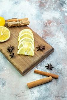 Bottom view fresh cut lemons cinnamon sticks anises on cutting board on nude table