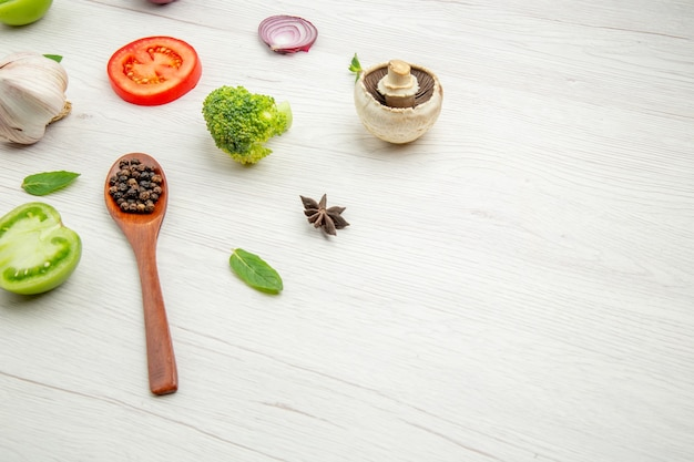 Vista dal basso cucchiaio di legno di verdure fresche tagliate con funghi al pepe nero pomodoro verde e rosso cipolla broccoli anice stellato su tavolo grigio con spazio libero