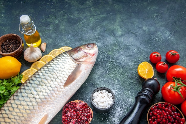 Vista dal basso pesce fresco pomodori macinapepe fette di limone sul tavolo da cucina