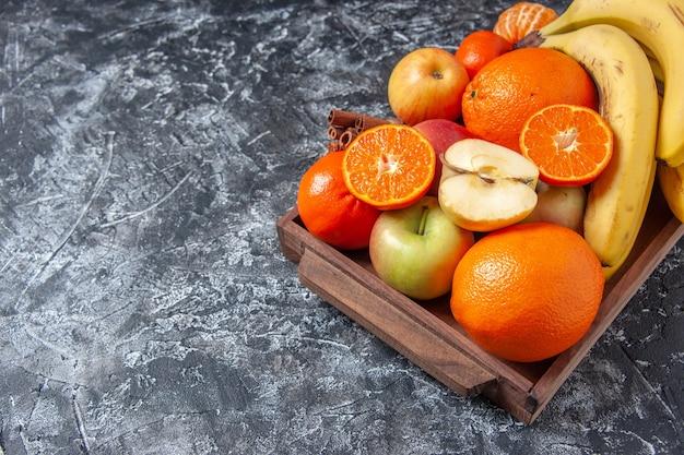 Vista dal basso frutta fresca e bastoncini di cannella sul vassoio di legno sullo spazio libero del tavolo