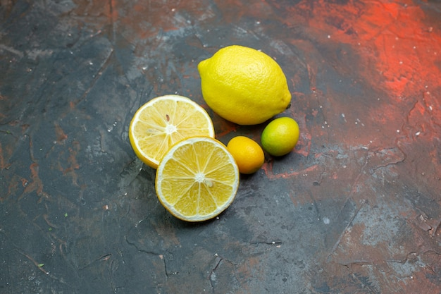 Bottom view fresh lemons cut lemons cumcuat on dark red ground free space