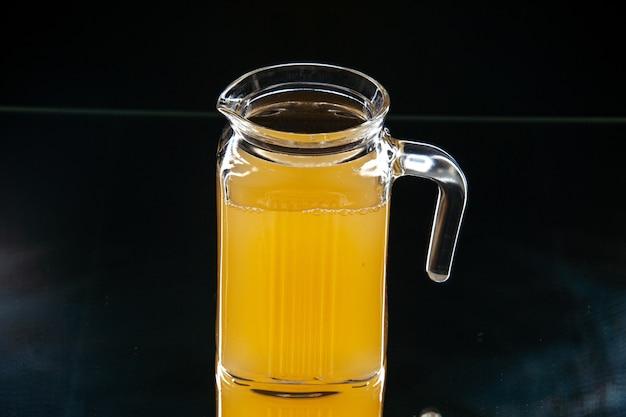 Вид снизу свежий ананасовый сок в графине на темном фоне копировать место