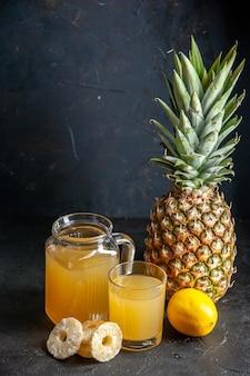 어두운 배경에 유리잔에 신선한 파인애플 주스와 물병 레몬