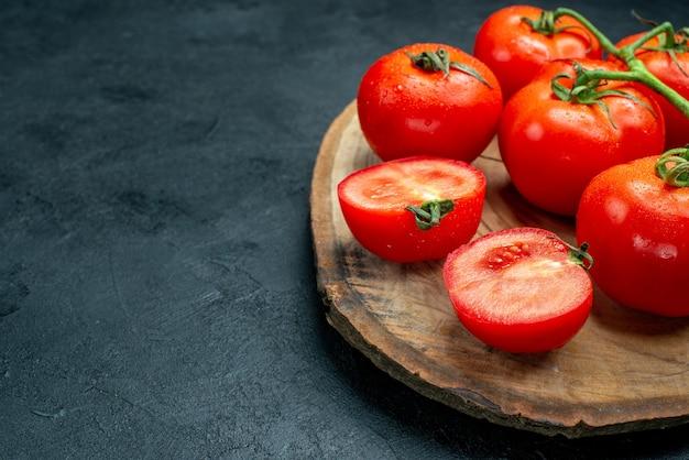 暗いテーブルの空きスペースに木の板に新鮮な赤いトマトの底面図
