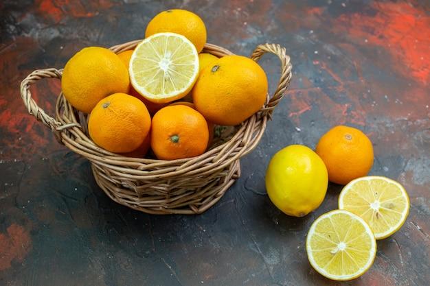 暗いテーブルの上の籐のバスケットの新鮮なレモンの底面図新鮮なタンジェリン