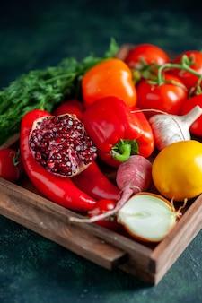 暗い上で木の板に新鮮な野菜と半分ザクロの底面図