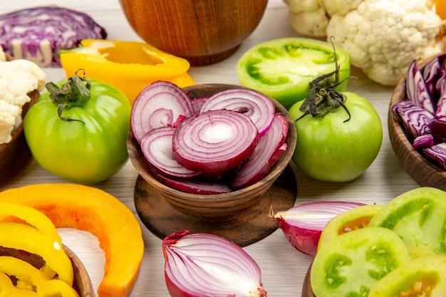 Vista dal basso verdure fresche peperoni pomodori verdi cavoli rossi cavolfiori zucche cipolle tagliate in ciotole su tavolo di legno bianco
