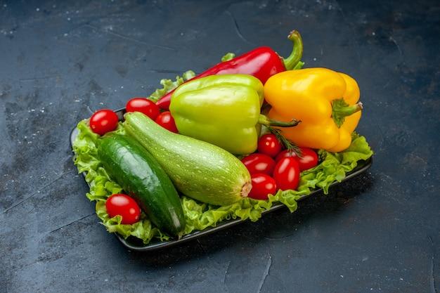 Vista dal basso verdure fresche peperoni zucchine pomodorini lattuga cetriolo sul tavolo nero