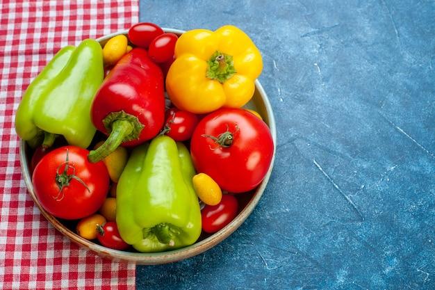 Vista dal basso verdure fresche pomodorini diversi colori peperoni pomodori cumcuat su piatto su tovaglia a quadretti rossa e bianca su tavolo blu spazio libero fotografia stock