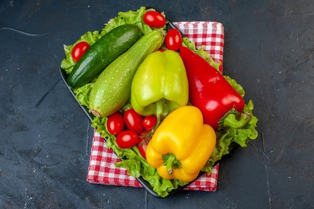 Vista dal basso verdure fresche peperoni colorati zucchine pomodorini cetriolo lattuga su piatto rettangolare nero tovagliolo a scacchi bianco rosso sul tavolo nero