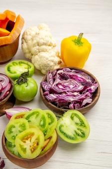 底面図新鮮な野菜は緑のトマトをカットし、ボウルに赤キャベツをカットします。白い木製のテーブルにピーマンのカリフラワーをカットします。