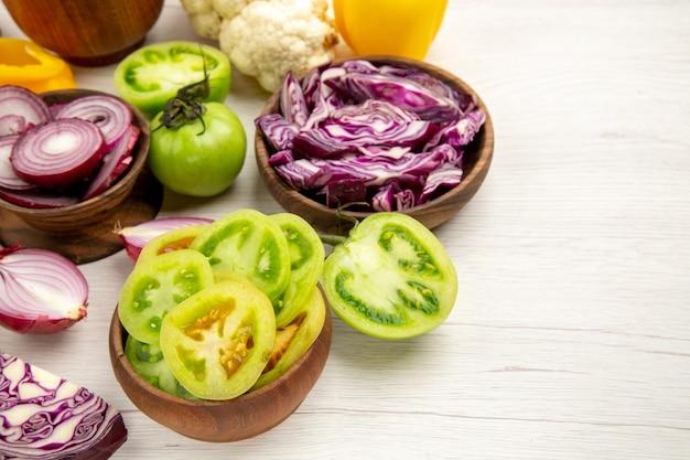Vista dal basso verdure fresche tagliate cipolla tagliata pomodori verdi tagliati cavolo rosso in ciotole cavolfiore peperone su tavolo di legno bianco