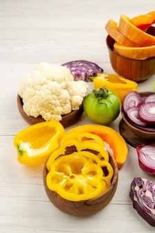 Vista dal basso le verdure fresche hanno tagliato le cipolle il pomodoro verde ha tagliato il cavolo rosso i peperoni gialli il cavolfiore in ciotole sul tavolo di legno bianco