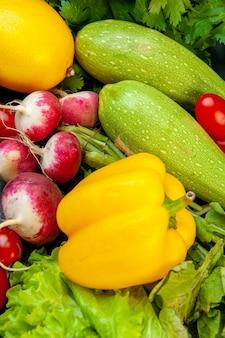 Vista dal basso verdure fresche lattuga ravanello zucchine prezzemolo pomodorini peperone giallo su superficie scura
