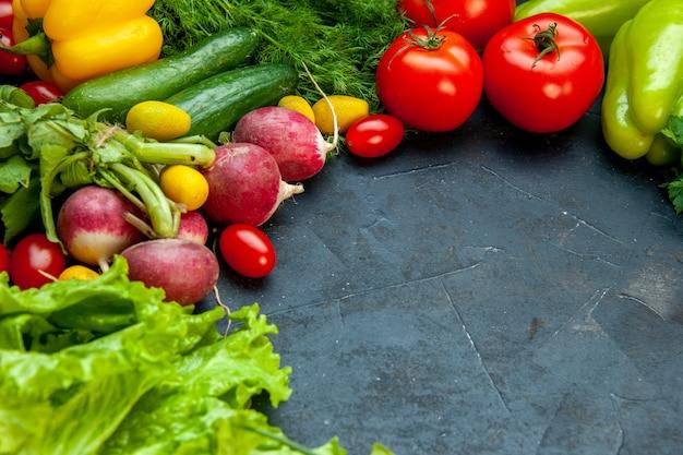 Vista dal basso verdure fresche lattuga pomodori ravanelli cetrioli aneto pomodorini su superficie scura copia posto
