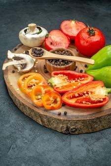 Vista dal basso verdure fresche funghi pepe nero in una ciotola cucchiaio di legno pomodori rossi peperoni su tavola di legno su tavola scura