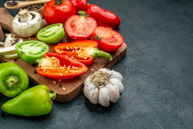 Vista dal basso verdure fresche funghi pomodori rossi e verdi peperoni sul tagliere aglio pepe nero in una ciotola sul tavolo scuro spazio libero