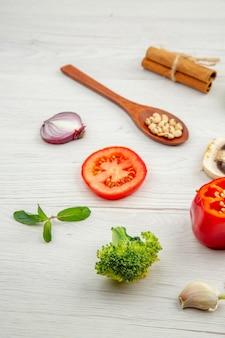 Vista dal basso verdure fresche cucchiaio di legno funghi pomodoro rosso cipolla broccoli aglio foglie di menta sul tavolo grigio