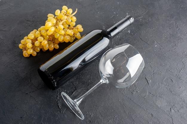 Вид снизу бутылка вина из свежего желтого винограда и стеклянная открывалка для вина на темном столе
