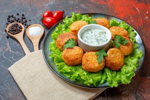 Вид снизу жареные шарики салата чи на тарелке с помидорами черри соль и черный перец в деревянных ложках на темном столе