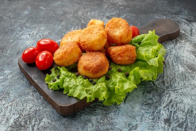 Вид снизу жареные сырные шарики, помидоры черри, салат на разделочной доске на сером фоне