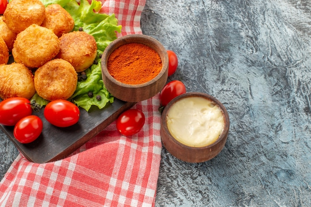 Palline di formaggio fritte vista dal basso spezie in piccole ciotole sul tagliere