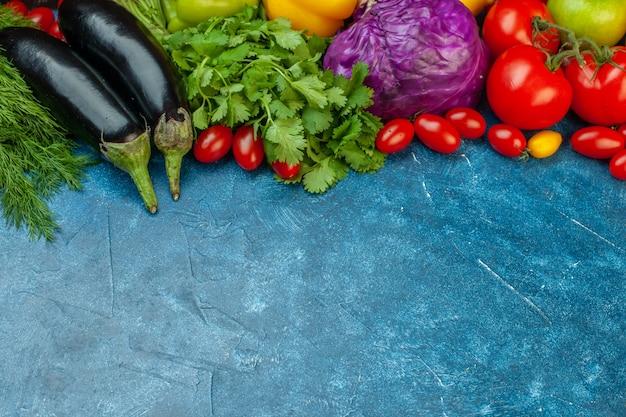 아래쪽 보기 과일 및 야채 체리 토마토 가지 토마토 붉은 양배추 고수풀이 여유 공간이 있는 파란색 테이블에 있습니다.