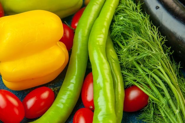 Vista dal basso frutta e verdura peperoni aneto peperoncino pomodorini sul tavolo blu