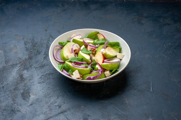 Insalata di mele verdi vista dal basso in una ciotola sul tavolo blu scuro con posto libero