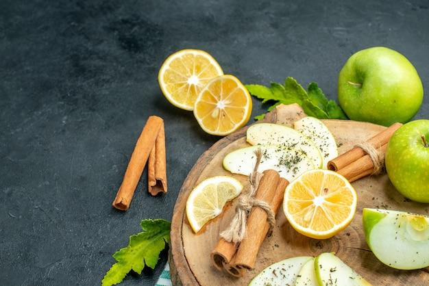 底面図青リンゴシナモンスティックとレモンスライス木の板のリンゴスライスは黒い地面にレモンリンゴをカットしました