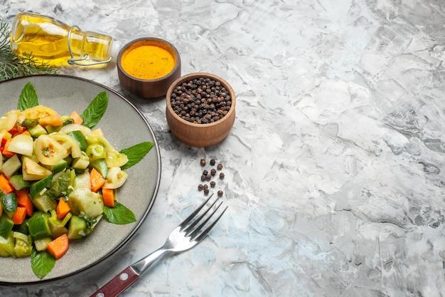 Вид снизу салат из зеленых помидоров на овальной тарелке вилка, миски с куркумой и черным перцем на темном фоне свободное пространство