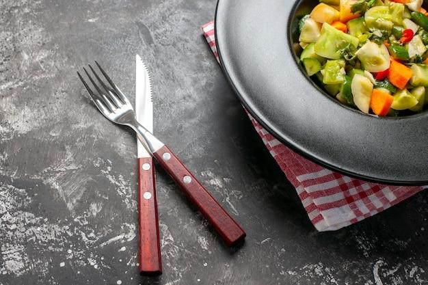 楕円形のプレートにグリーントマトのサラダを交差させ、暗い背景にナイフを下から見た図