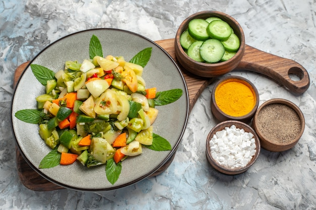 Вид снизу салат из зеленых помидоров на овальной тарелке на разделочной доске разные специи на темном фоне