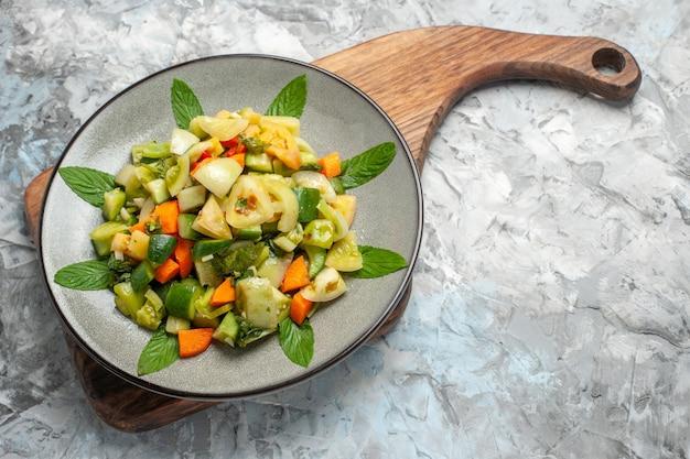 Вид снизу салат из зеленых помидоров на овальной тарелке на разделочной доске на темном фоне