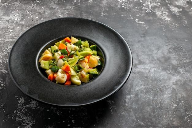 어두운 배경에 타원형 접시에 아래쪽 보기 녹색 토마토 샐러드
